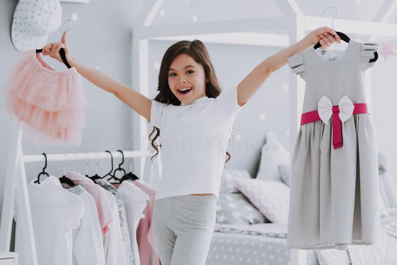 选择一件礼服的小逗人喜爱的女孩在卧室 库存照片
