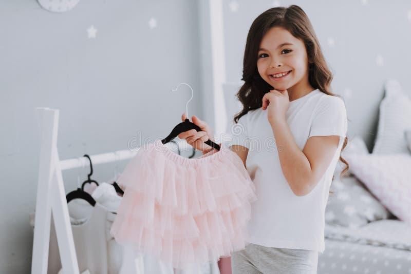 选择一件礼服的小逗人喜爱的女孩在卧室 免版税库存图片
