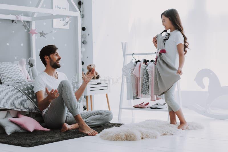 选择一件礼服的父亲帮助的女孩在卧室 库存图片
