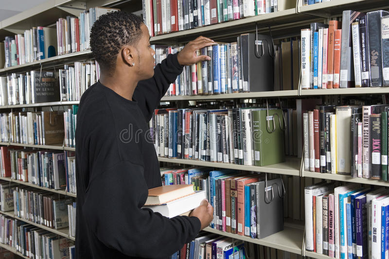 选择书的人从架子 免版税库存图片