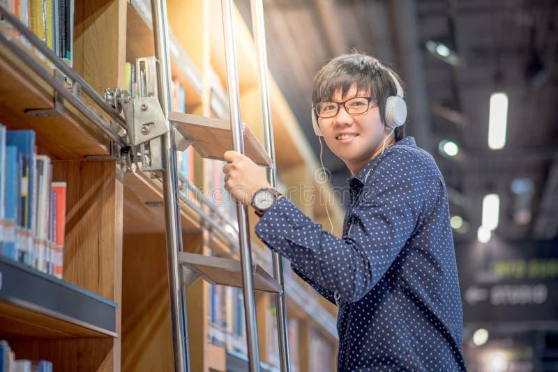 选择书的年轻亚裔人使用梯子在图书馆里 库存照片