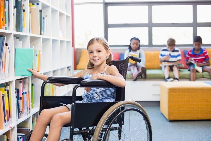 选择书的残疾学校女孩从书架在图书馆里 免版税库存图片