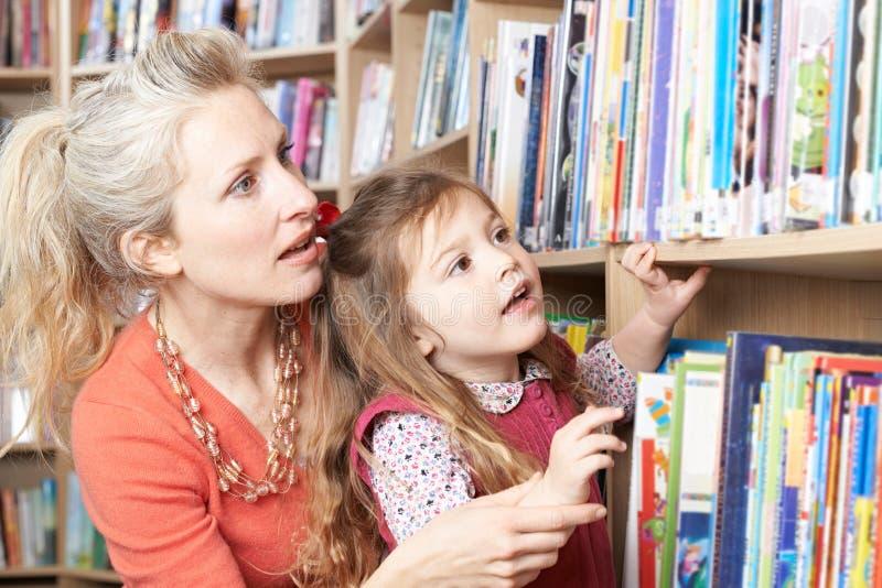 选择书的母亲和女儿从图书馆架子 库存图片