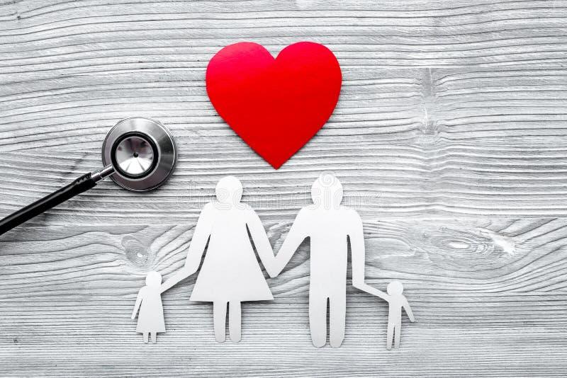 选择健康保险 听诊器、纸家庭心脏和剪影在灰色木背景顶视图copyspace的 库存图片
