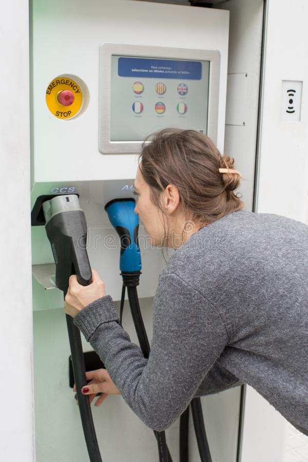 选择充电器的妇女在一个充电站 免版税库存照片