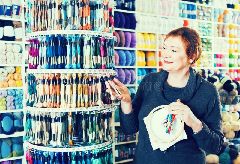 选择刺绣的妇女mouline在针线商店 库存照片
