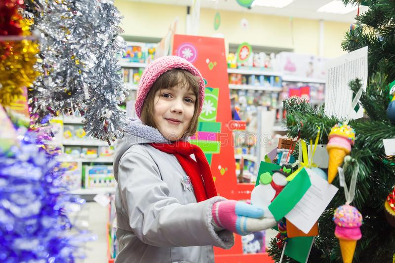 选择圣诞树的女孩对于儿童` s物品商店 免版税库存照片