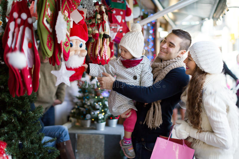 选择圣诞节装饰的愉快的家庭在圣诞节市场上 免版税库存照片