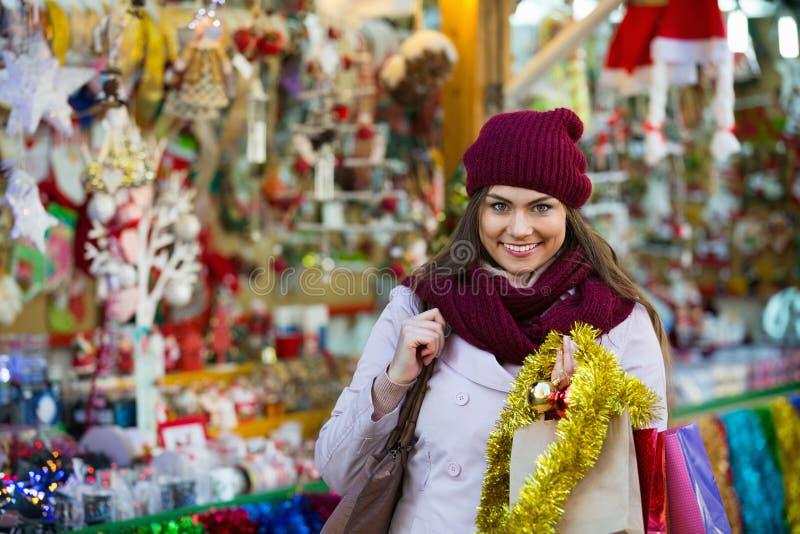 选择圣诞节装饰的美丽的快乐的微笑的妇女 库存图片