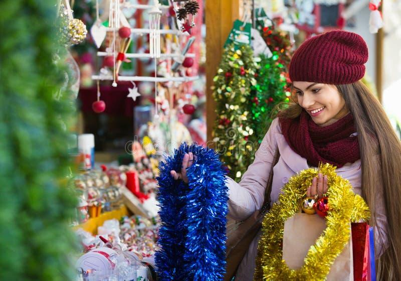 选择圣诞节装饰的美丽的快乐的微笑的妇女 免版税库存照片