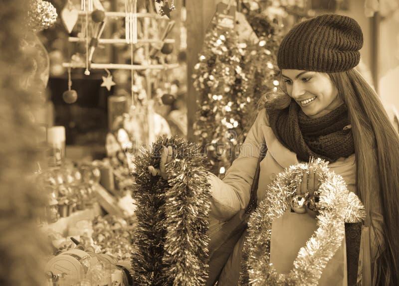选择圣诞节装饰的美丽的快乐的微笑的妇女 图库摄影