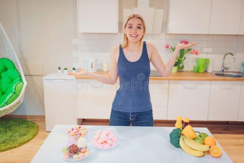 选择在健康和不健康的食物之间的蓝色T恤杉的年轻微笑的妇女在厨房里 困难的选择之间 库存图片