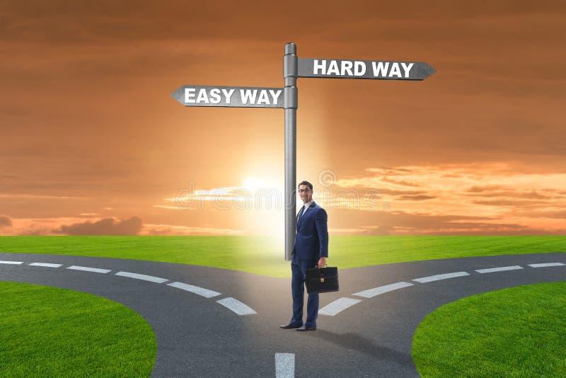 选择在坚硬和容易的方法之间的商人 免版税库存图片