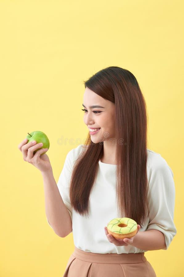 选择在多福饼和绿色苹果之间的年轻亚裔妇女在黄色背景 库存图片