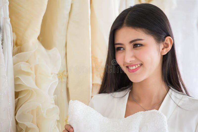 选择在时尚商店婚姻的沙龙的年轻亚裔新娘秀丽画象婚纱,豪华 ?? 库存照片