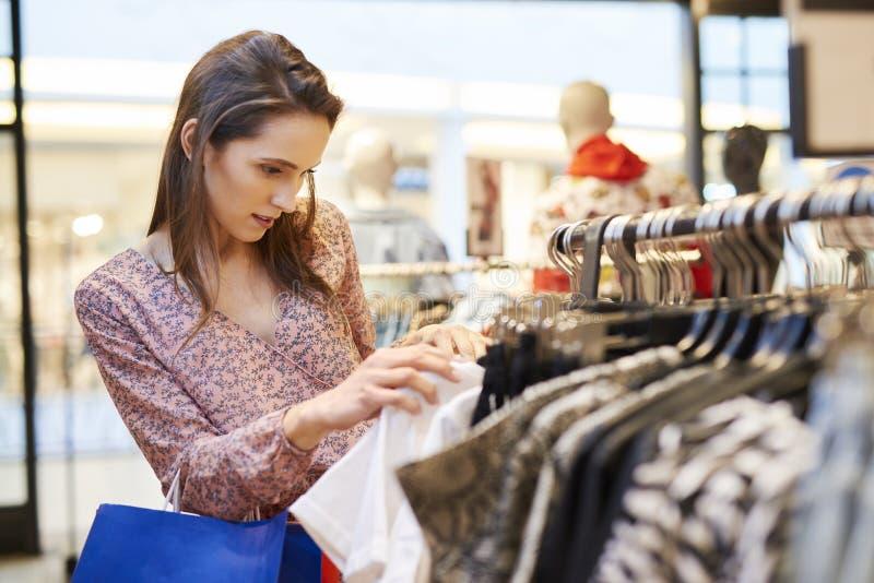 选择在服装店的年轻女人女衬衫 库存图片