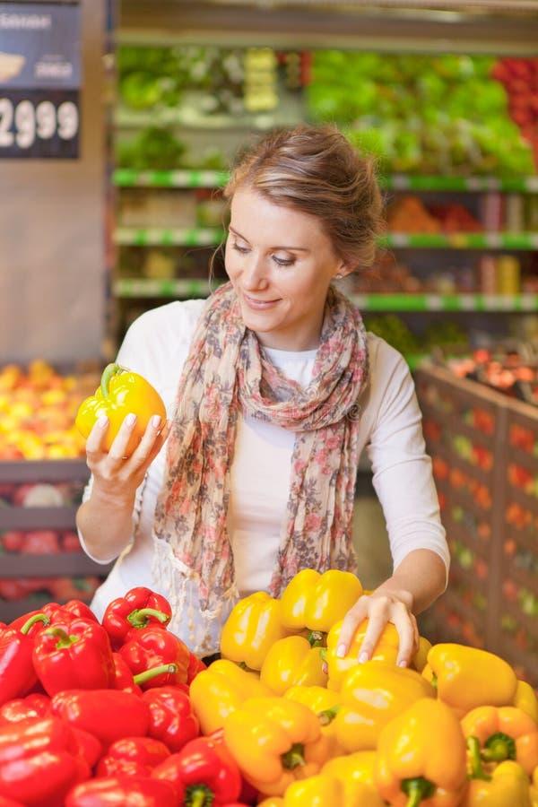 选择在杂货的美丽的少妇画象菜 免版税图库摄影