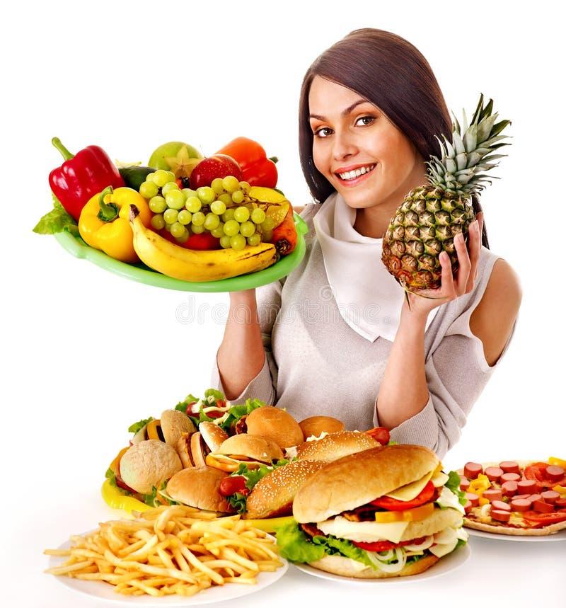 选择在果子和汉堡包之间的妇女。 免版税库存照片