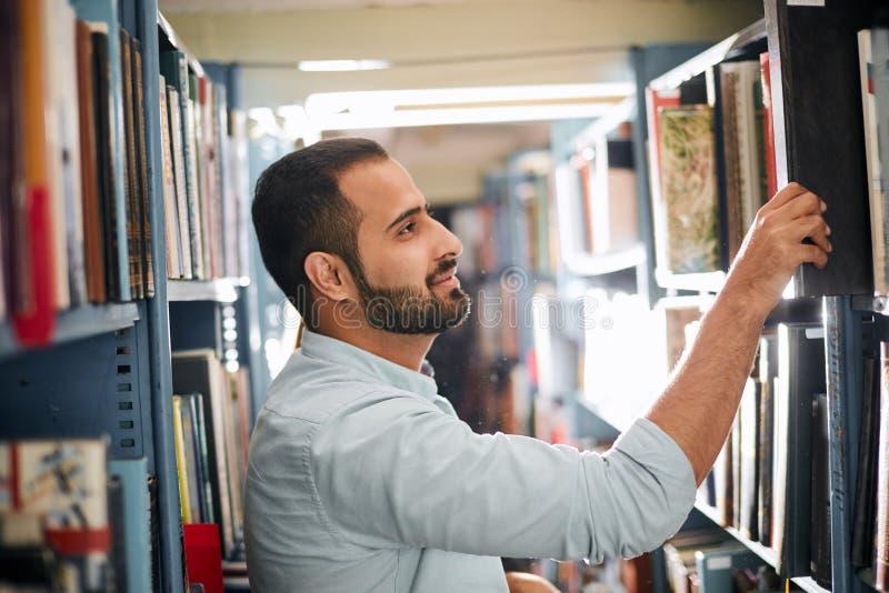 选择在架子之间的年轻阿拉伯有胡子的男生书在图书馆里 库存图片