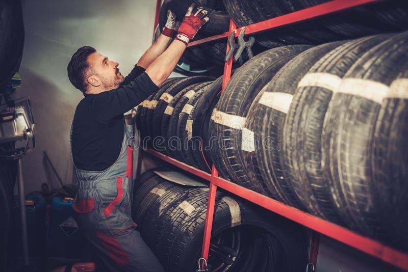 选择在汽车修理服务的专业汽车修理师新的轮胎 库存图片