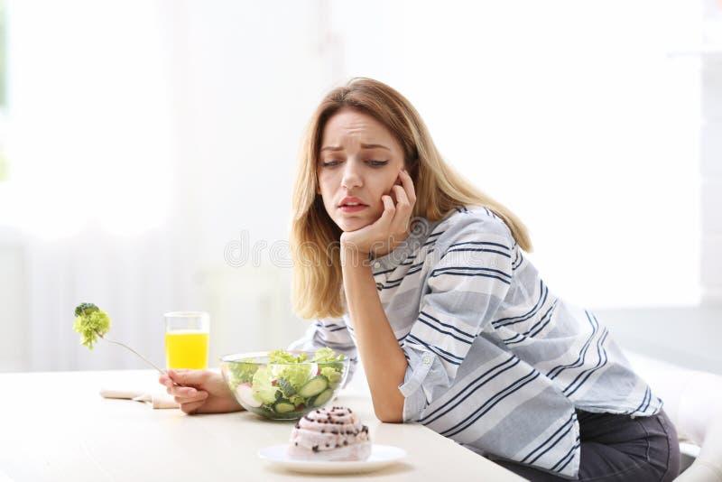 选择在菜之间的不快乐的妇女 免版税库存照片