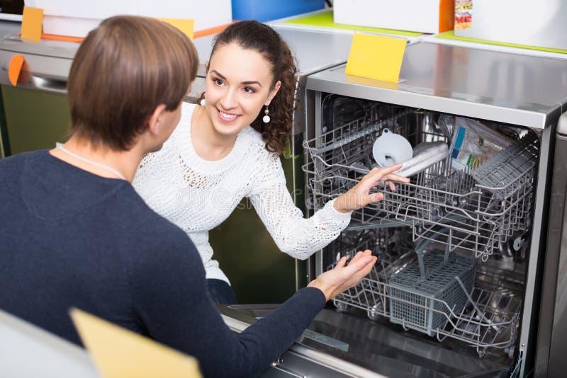 选择在装置sto的年轻夫妇新的盘洗衣机 免版税库存图片