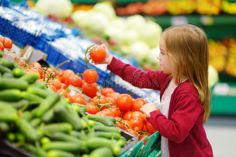 选择在食品店的小女孩蕃茄 免版税库存图片