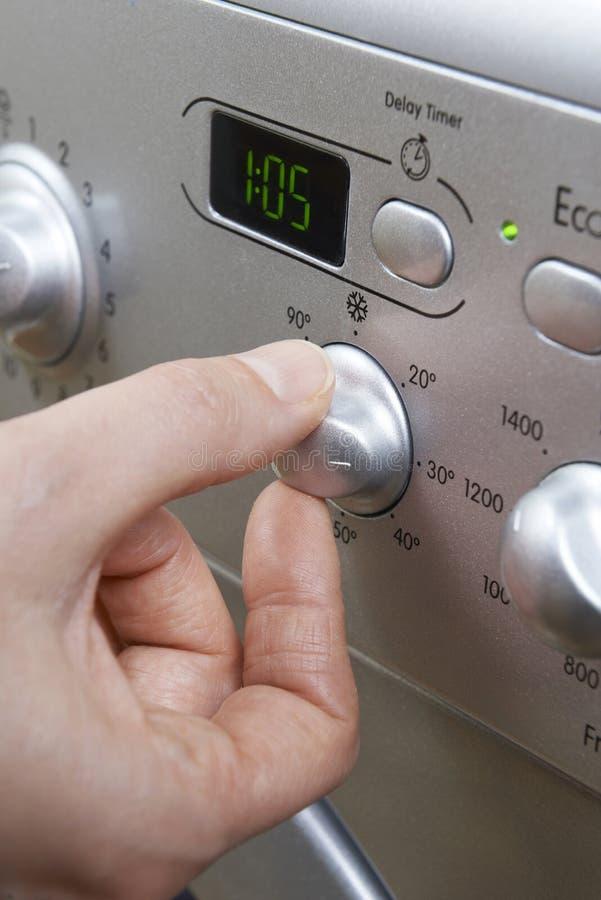 选择在洗衣机的妇女更加凉快的温度保存En 免版税库存图片