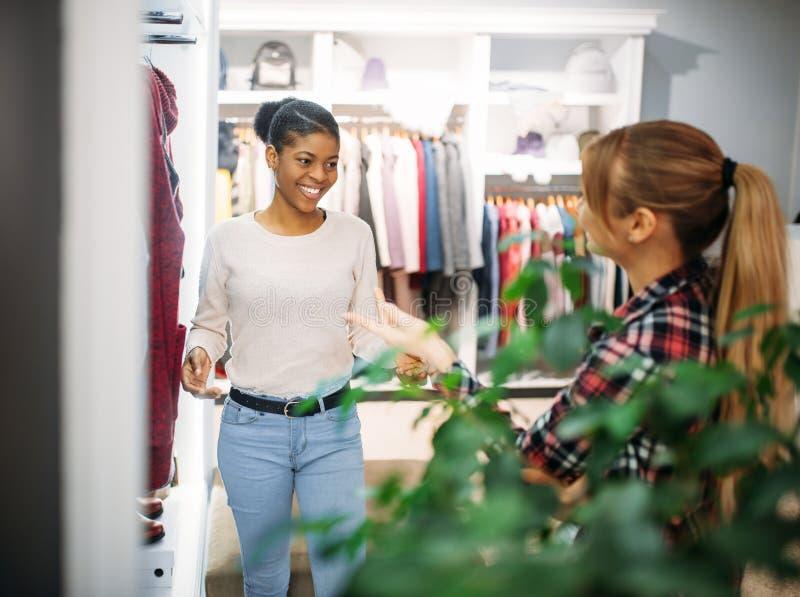 选择外套的两个女性朋友在商店,购物 免版税库存图片