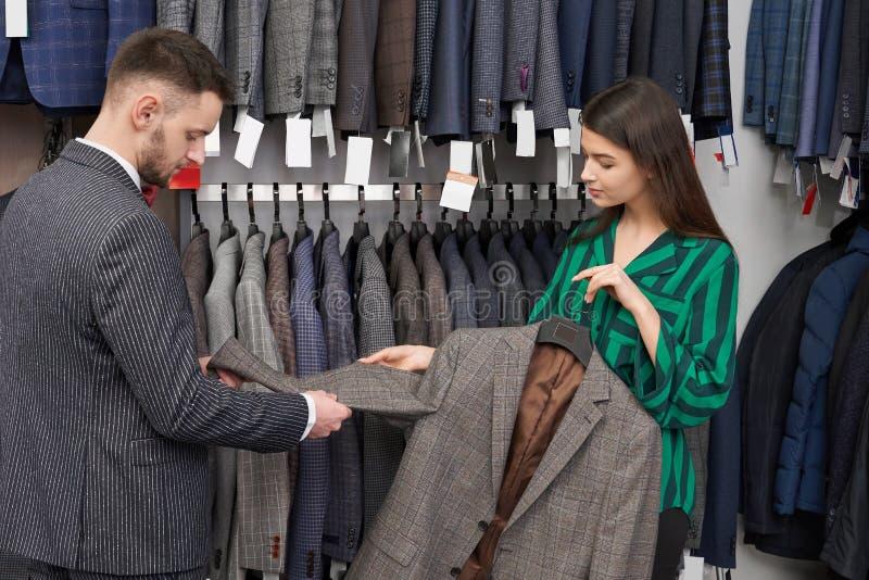 选择夹克的年轻人在有助理的商店 库存图片