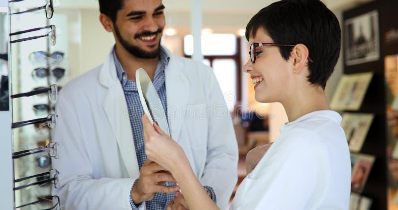 选择她新的玻璃的妇女在光学商店在眼科医生帮助下  库存图片