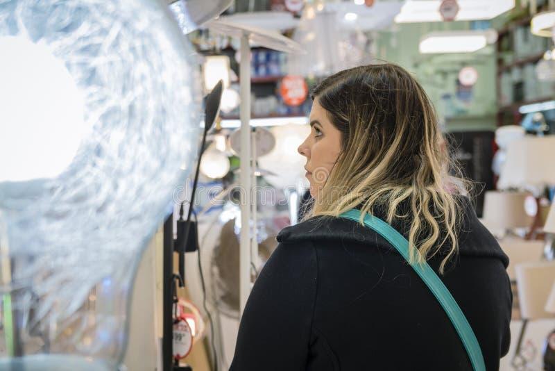 选择她的公寓的妇女正确的灯在家用家具零售店的照明设备部门 免版税库存图片