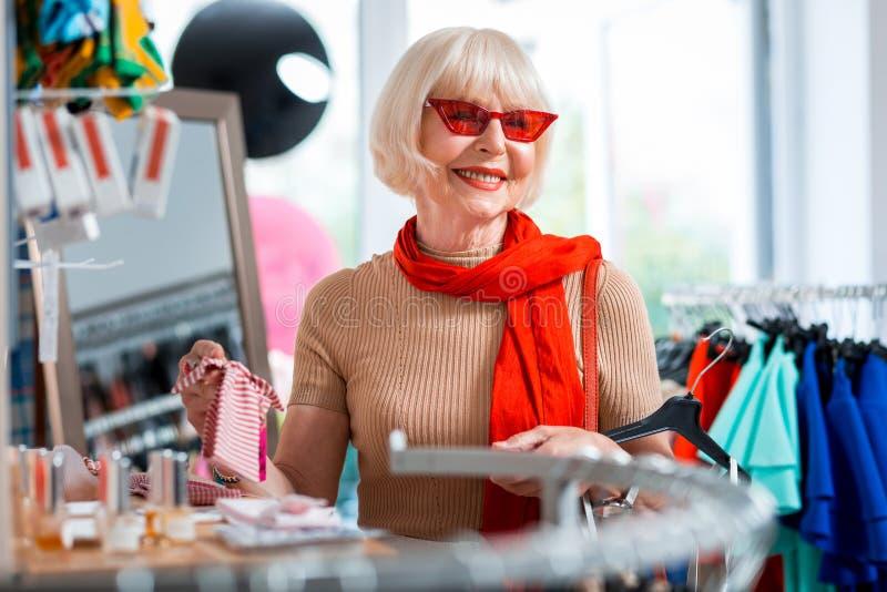 选择她的礼服的快乐的年长妇女一个头饰带 免版税图库摄影