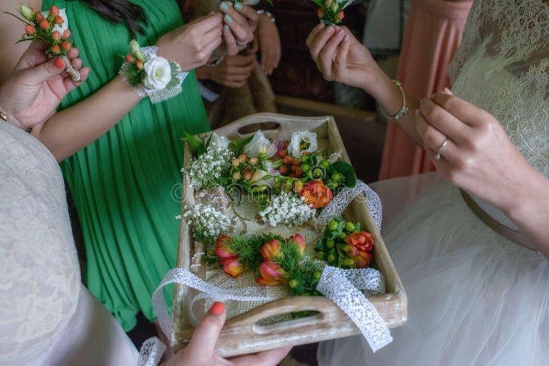 选择小苍兰和莓果钮扣眼上插的花的女傧相为婚礼客人 库存照片