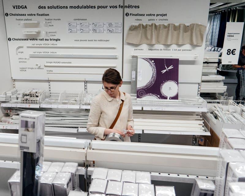 选择帷幕辅助部件的妇女在宜家商店 免版税库存图片