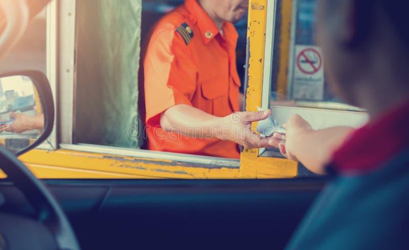 选择性地关注高速公路的司机薪酬 男子向收费公路收费门高速公路入口的收银员付款 库存照片