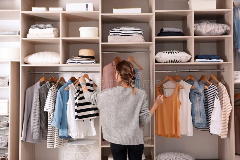 选择成套装备的妇女从与时髦的衣裳的大衣橱壁橱 免版税库存图片