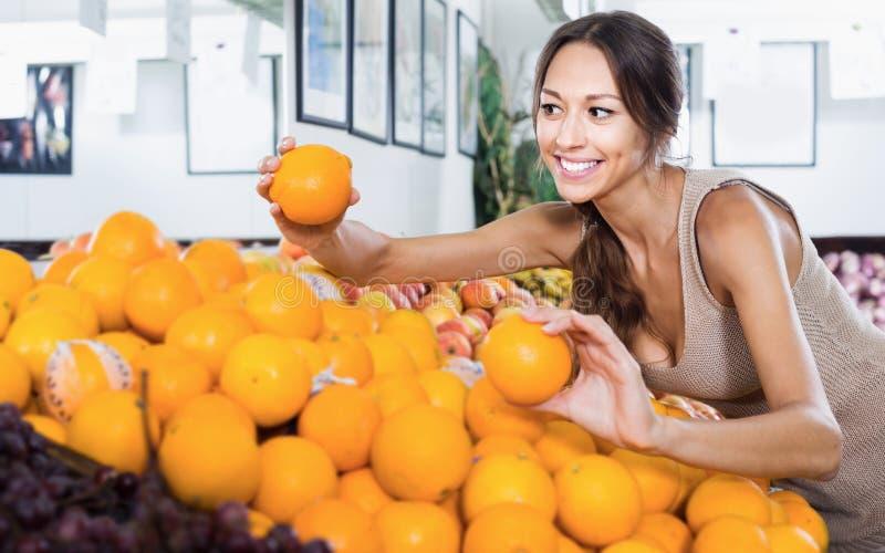 选择成熟桔子的年轻快乐的妇女顾客 免版税图库摄影