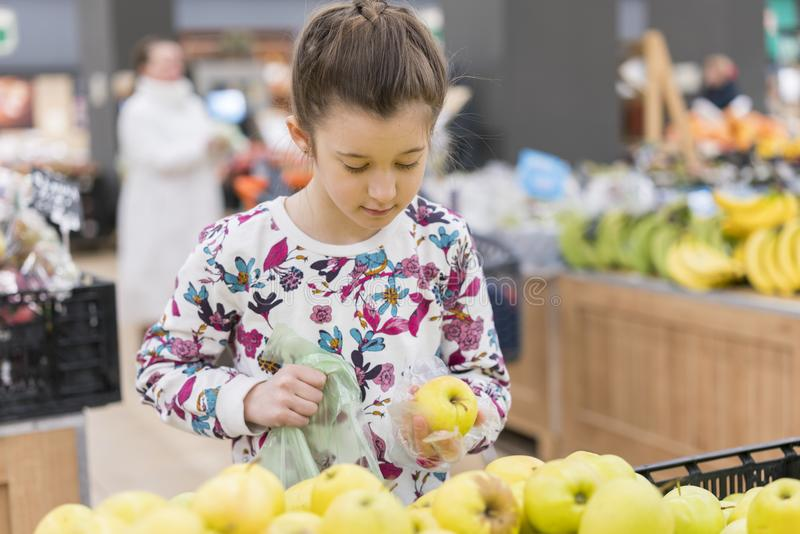选择成熟苹果的小女孩在食品店或超级市场 库存照片