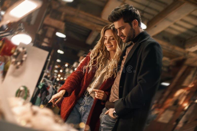 选择手工制造仿制首饰的愉快的年轻夫妇在小街市上 图库摄影