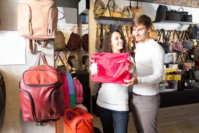 选择提包的年轻家庭在男子服饰用品商店 免版税库存照片