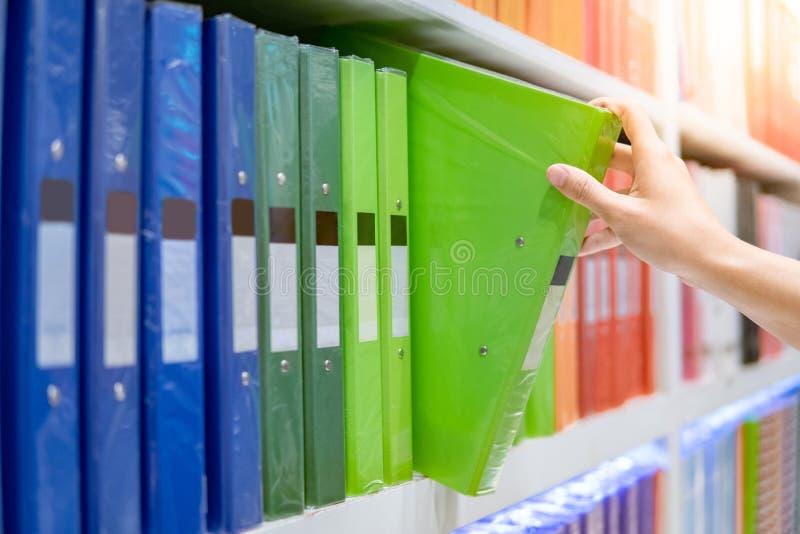 选择文件夹的男性手在文具店 免版税图库摄影