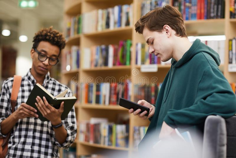 选择文学的年轻学生男孩在图书馆里 免版税库存照片