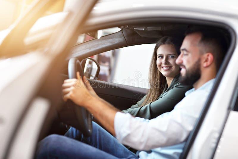 选择新的汽车的成人夫妇在陈列室里 库存图片