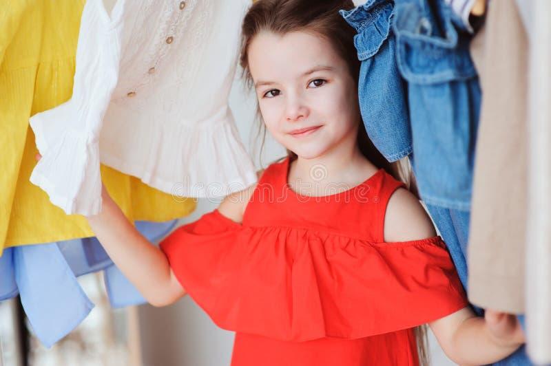 选择新的现代衣裳的逗人喜爱的小孩女孩在她的衣橱或商店试装间 免版税库存照片