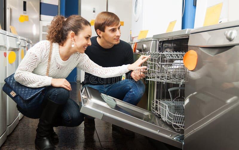 选择新的盘洗衣机的家庭 免版税库存照片