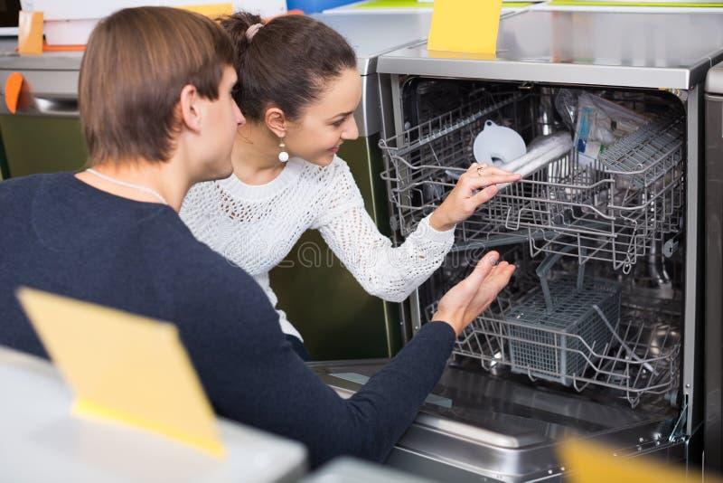 选择新的盘洗衣机的年轻家庭在超级市场 免版税库存图片
