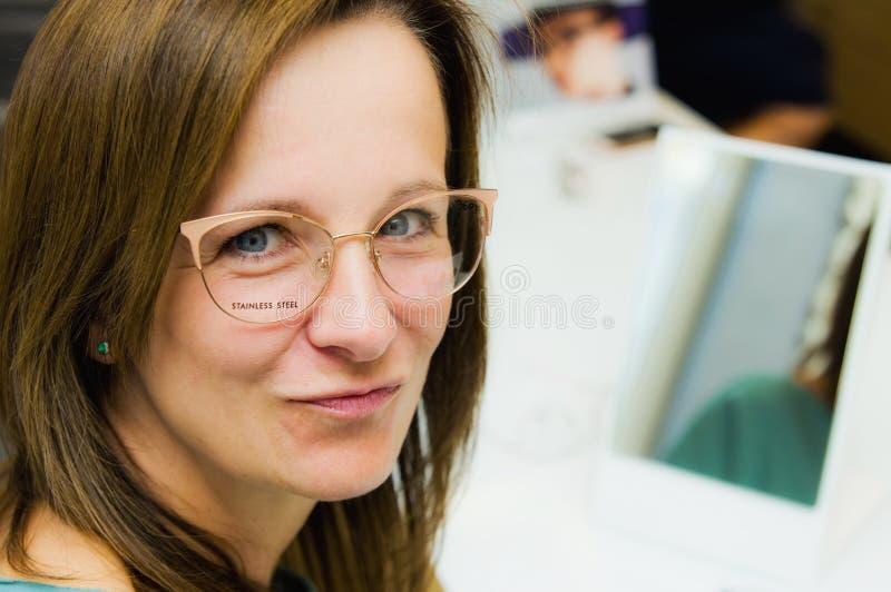 选择新的镜片的端庄的妇女在眼镜师商店 免版税图库摄影