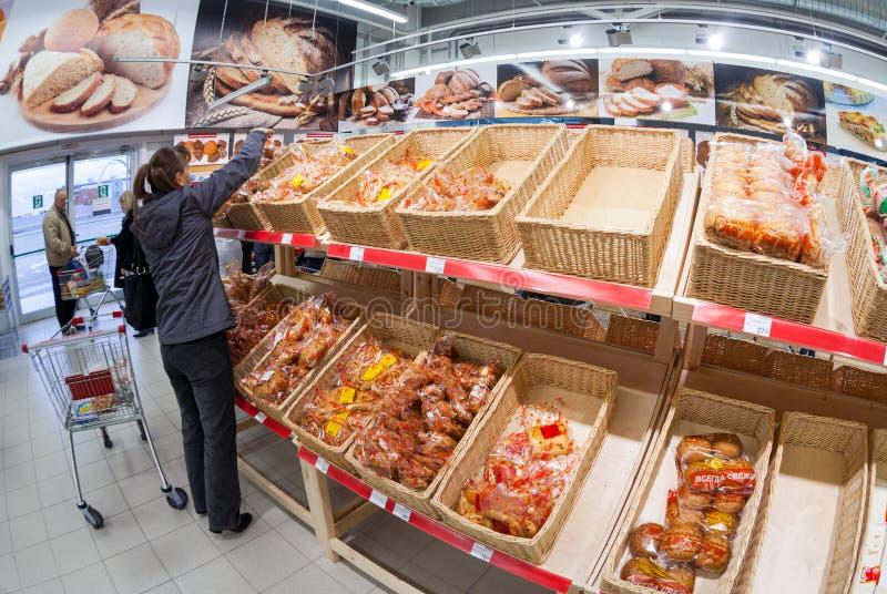 选择新鲜的面包店产品的少妇 免版税库存图片