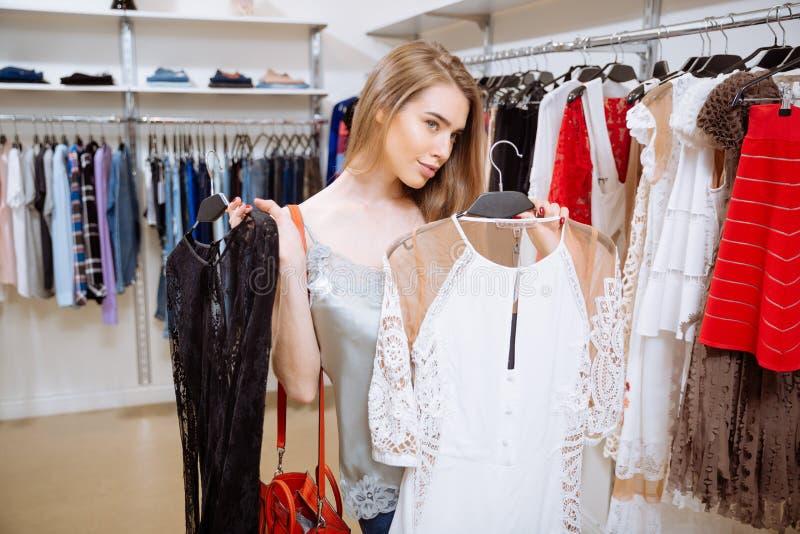 选择晚礼服的微笑的妇女在衣物商店 免版税库存照片